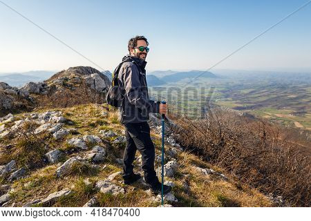 Traveling outdoor hiking in nature. Traveling in nature. Man hiker outdoor in nature. Nature. Hiker. Hiking. Nature and beautiful mountain view. man hiker sitting on mountain cliff in nature.