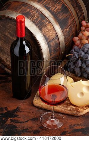 Wine bottle, grapes, cheese, glass of red wine and old wooden barrel