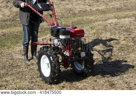 A Farmer Man Plows The Land With A Cultivator. Machinery Cultivator For Soil Cultivation In The Gard