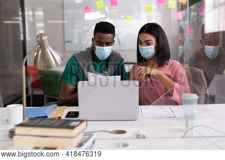 Diverse creative colleagues wearing face masks brainstorming in meeting room. independent creative design business during covid 19 coronavirus pandemic.