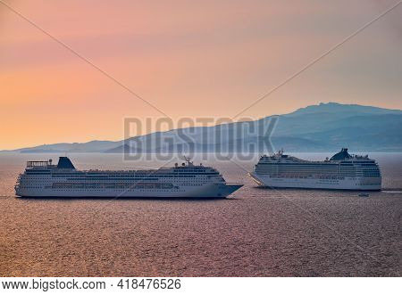 Two Big Tourist Cruise Liners Manoeuvre In Harbor. Beautiful Sunset Sky. Colorful Shot At Golden Hou