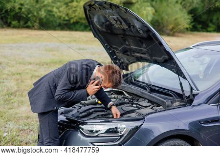 Elegant Young Business Man Trying To Fix Car Breakdown Or Engine Failure And Waiting For Towing Serv