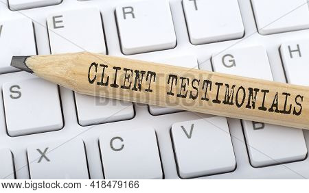 Text Client Testimonials On Wooden Pencil On White Keyboard. Business