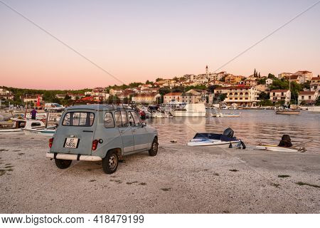 Seget Donji, Croatia - September 9, 2019: Vintage car parked in small harbour of the Mediterranean town Seget Donji near the Trogir town at Adriatic coast at sunset, Croatia