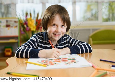 Smiling Preschool Boy Draws In His Notebook. The Boy Sits At The Table And Holds A Pencil In His Han