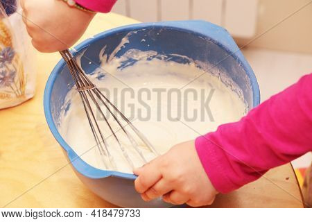 Little Girl Helps To Prepare Dough For Baking Pies. The Girl Helps Her Mother To Cook.