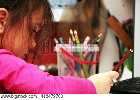 A Little Girl Draws Colorful Pictures And Plays With Children With Crayons Sitting At A Table Indoor