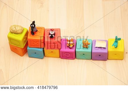 Child Girl Plays With Toys At Home, In Kindergarten Or Nursery. Little Girl Plays With Colored Cubes