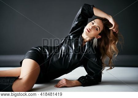 Trendy Sensual Young Woman In Black Cloth Posing Over Studio Background