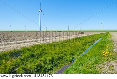 Wind Turbines For Renewable Energy In An Agricultural Field In Bright Blue Sunlight In Spring, Noord