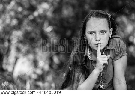 Teengirl with her finger over her mouth. Hushing. Black and white photo.