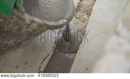 The Solution Is Poured Into The Gap In The Floor. Dark Bucket. Floor Leveling Solution. A Bucket Fro