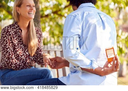 Mature Man Kneeling And Holding Engagement Ring Behind Back About to Propose To Woman In Park