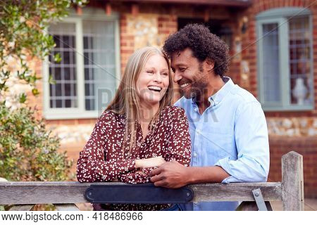 Portrait Of Loving Couple By Gate Holding House Keys Outside New Home In Countryside