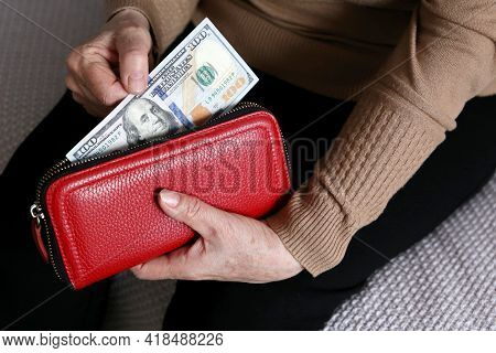 Elderly Woman Takes Out Us Dollars From Her Red Wallet. Concept Of Pension Payments In Usa, Financia