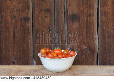 Harvest Bunch Of Tasty Red Bio Tomatoes In White Bowl. Delicious Fresh And Juicy Vegetables From Far