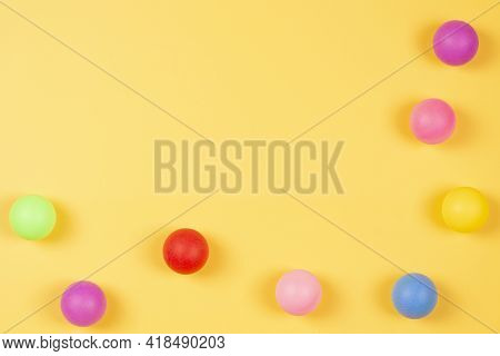 Multi Colored Plastic Colorful Balls On Yellow Background. Top View