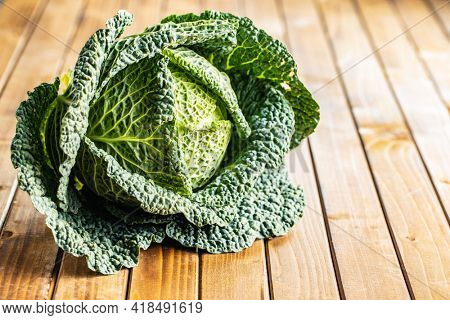 Green savoy cabbage on wooden table.
