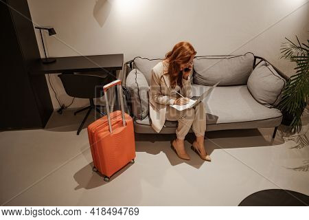 Business Trip Concept. A Very Busy Red-haired Female Model In A Stylish Business Suit And An Orange