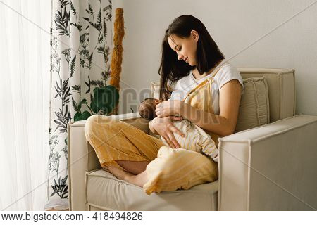 Newborn Baby Boy Sucking Milk From Mothers Breast. Portrait Of Mom And Breastfeeding Baby.