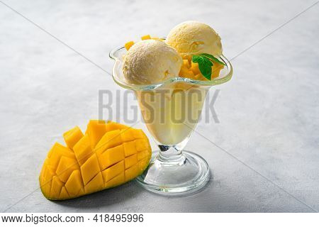 Creamy Mango Ice Cream And Fresh Mango On A Gray Background. Side View, Copy Space. Summer Fruit Des