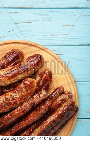Grilled Sausages On Wooden Board On Blue Background. Top View