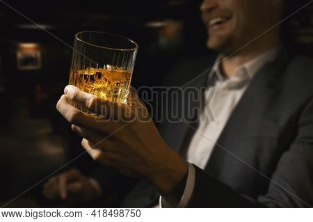 Happy Businessman With Glass Of Whiskey In Gentlemen Club Bar