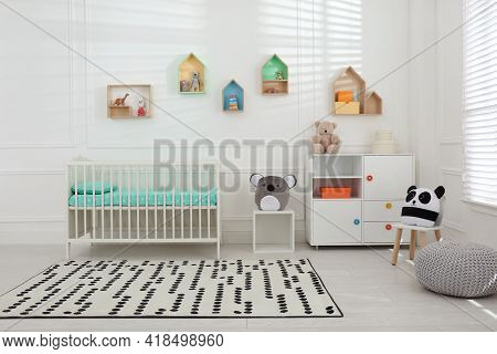 Comfortable Crib Near Wall With Color Shelves In Baby Room. Interior Design