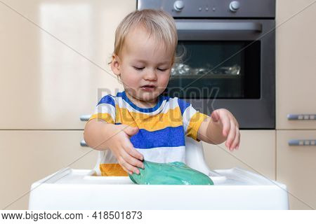 Child Play With Slime At Home In The Kitchen. Little Toddler Boy Squeeze And Stretching Green Slime
