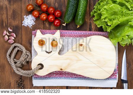 Cutting Wooden Board In The Form Of A Cat On A Wooden Table. Cherry Tomato Eyes And A Peppercorn Smi
