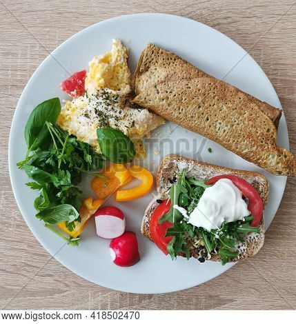 A Healthy And Nutritious Breakfast. Scrambled Eggs, Pancake, Brown Bread Sandwich, Vegetables And Gr