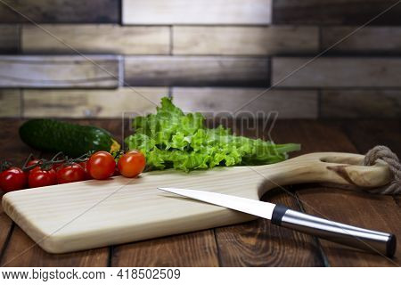Cutting Board On A Wooden Table. Handmade Chopping Board. Fresh Vegetables And Cutting Board.