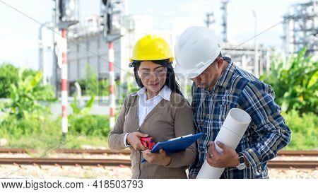 Engineers Woman And Supervisor Man Holding Blueprint And Discussion Report Schedule For Workers Secu