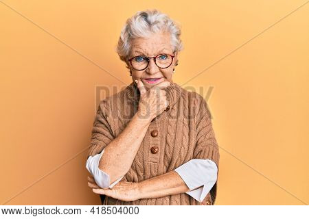 Senior grey-haired woman wearing casual clothes and glasses looking confident at the camera smiling with crossed arms and hand raised on chin. thinking positive.