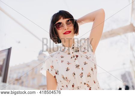 Attractive Young Woman In Elegant Sunglasses Posing With Romantic Smile. Outdoor Portrait Of Short-h