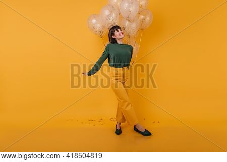 Inspired Woman With Trendy Haircut Looking Away While Posing With Party Balloons. Indoor Photo Of Am
