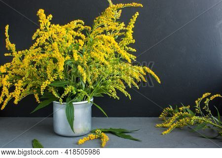 Bouquet Of Canadian Goldenrod In An Aluminum Mug On A Gray Background, Twigs With Delicate Yellow Fl
