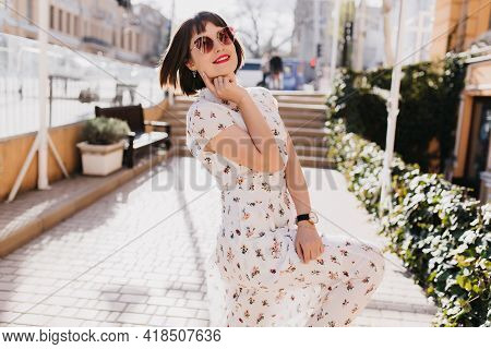 Pleased White Woman In Trendy Summer Dress Dancing On The Street. Outdoor Photo Of Smiling Female Mo