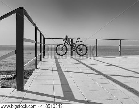 Alone Bicycle At The Seafront Fence In Sunny Day Against Sea And Sky