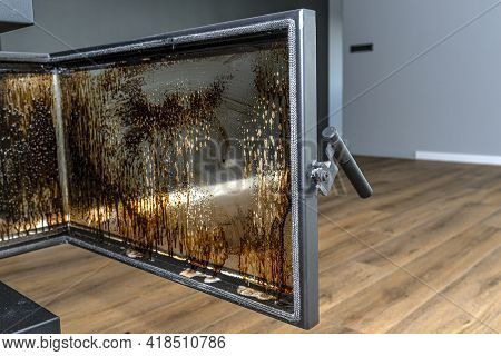 Cleaning The Corner Glass From Soot In A Modern Fireplace With A Closed Combustion Chamber Standing