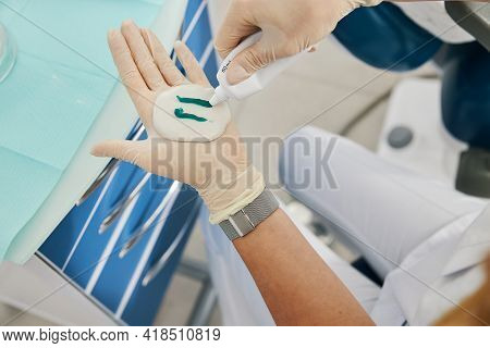 Orthodontist Leaving Two Stripes Of Gel On Dental Cast Putty