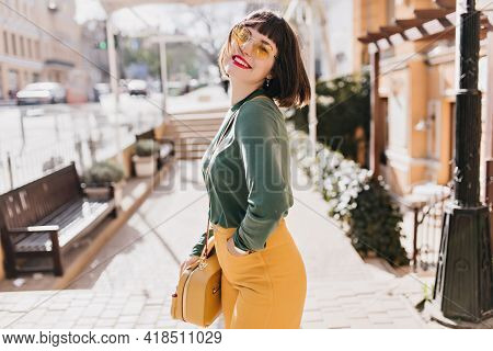 Dreamy White Woman With Trendy Handbag Laughing On Urban Background. Outdoor Photo Of Amazing Brunet