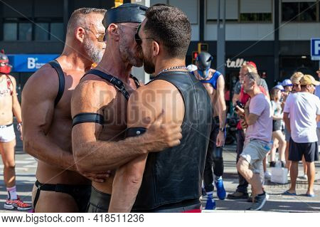 LGTBQ Pride Festival celebration. Barcelona - Spain. June 29, 2019: Two mature gay men dressed in fetish outfit kiss each other on gay parade