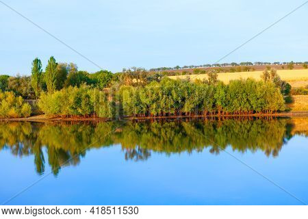 Coastal Parkland Scenery . Green Trees Growing On The Riverside . Idyllic Nature Reflection In The L