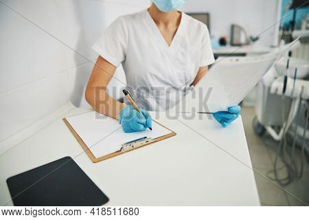 Female Dentist Reading X-ray And Writing Notes