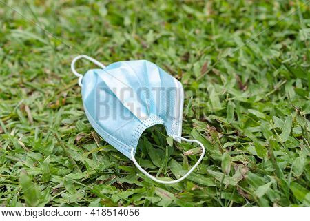 Dirty Used Medical Face Mask For Protection For Coronavirus Lying On Green Grass. A Facial Surgical