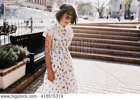 Gorgeous Young Woman In Cute Retro Dress Enjoying Sunny Morning. Outdoor Photo Of Chilling Brunette