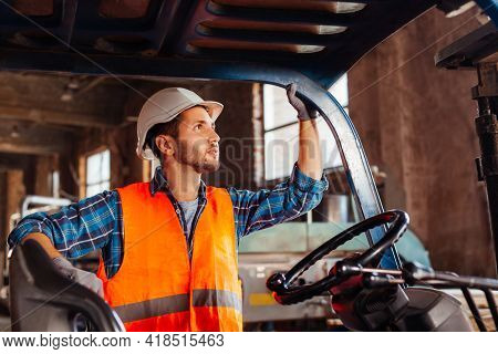 Young Confident Warehouse Worker Posing In A Forklift Truck