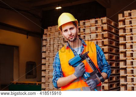 Professional Woodworker In Hardhat Holding Pneumatic Hammer