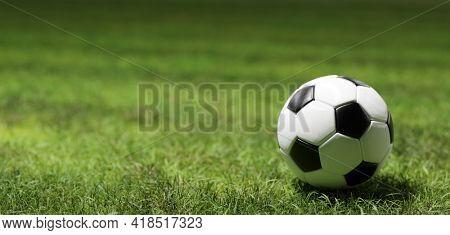 Football soccer ball on grass field in spotlight 3d illustration